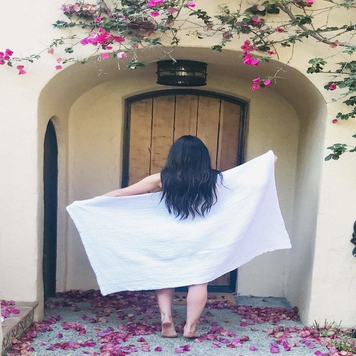 A model with their back facing the camera with the bath sheet stretch out behind to show the large size