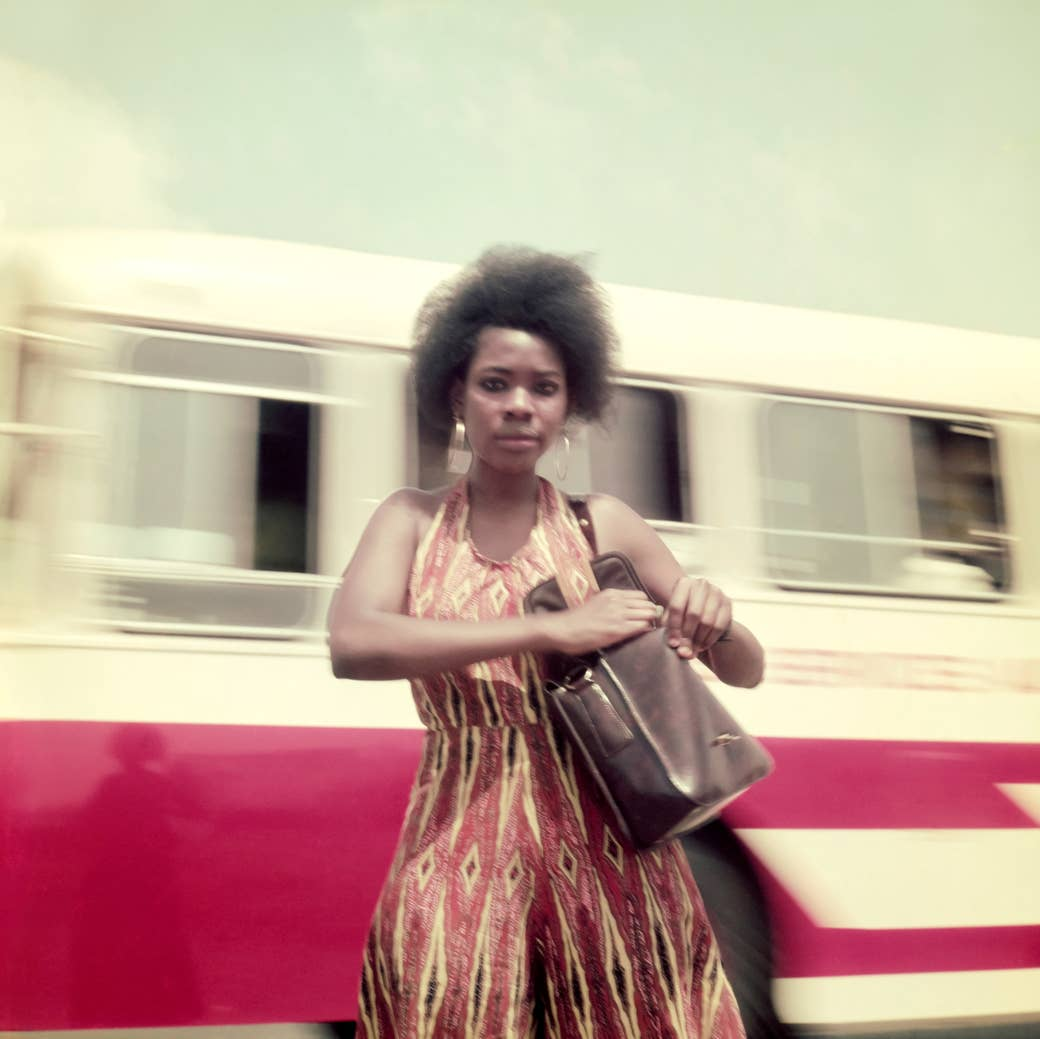 A woman in a colorful dress in front of a moving bus