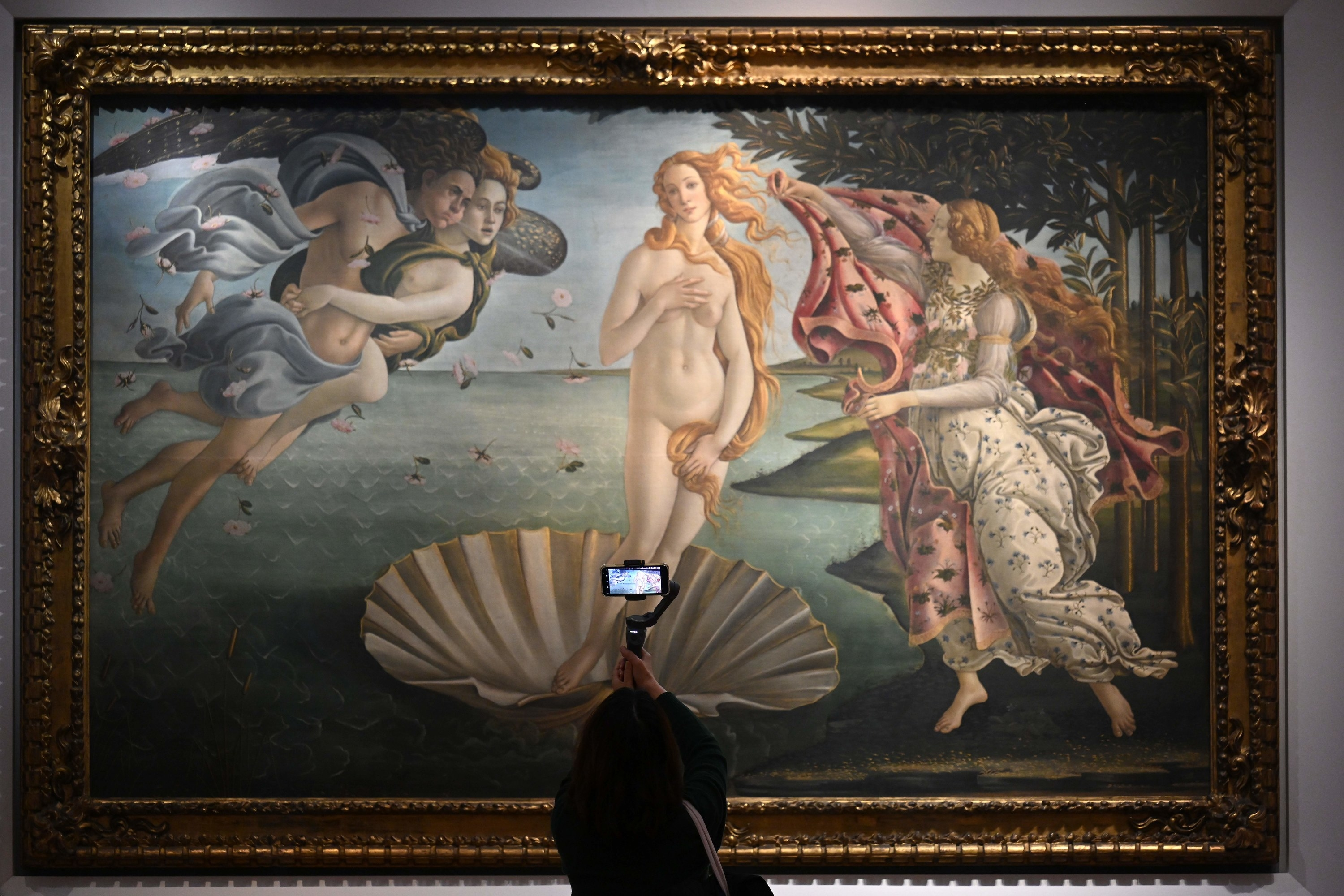 A woman taking a picture of Boticelli's Venus with her cell phone