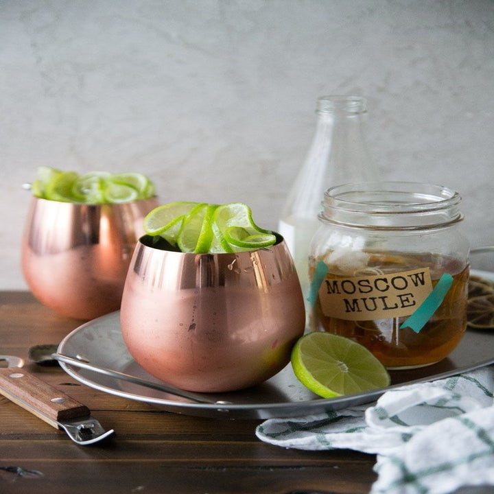 a moscow mule cocktail in a mason jar next to two copper cups