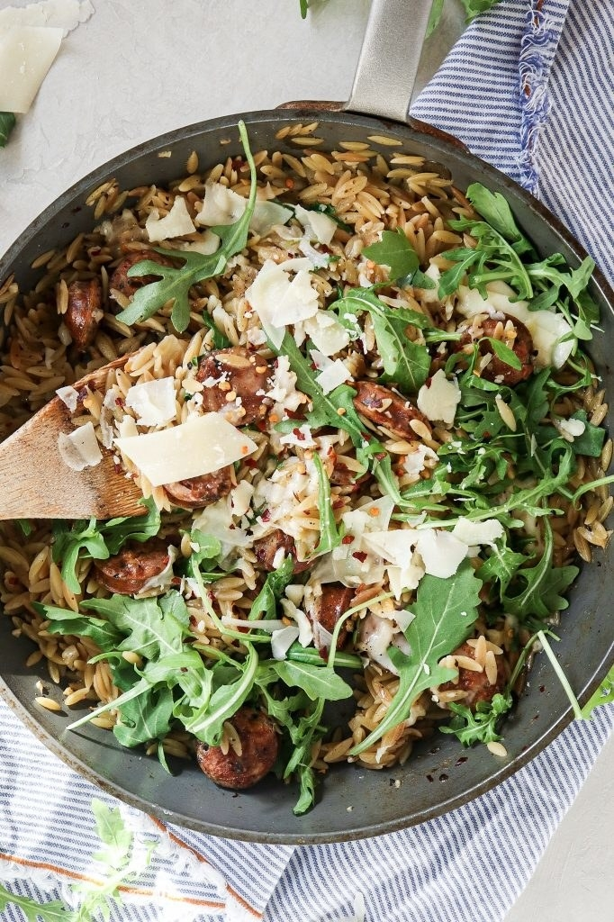 A skillet with orzo, arugula, and chicken sausage.