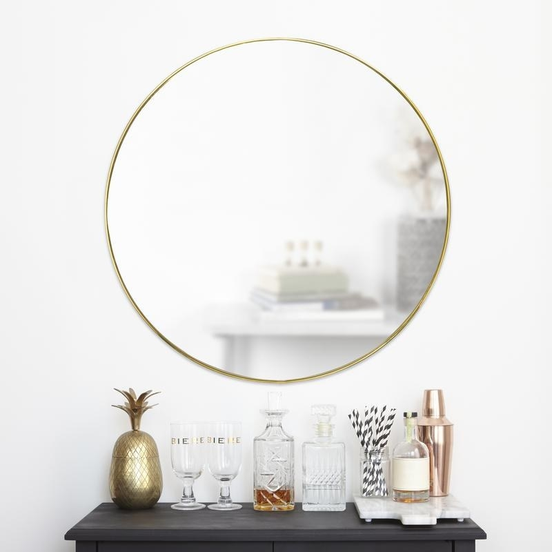 round gold mirror hanging on a wall