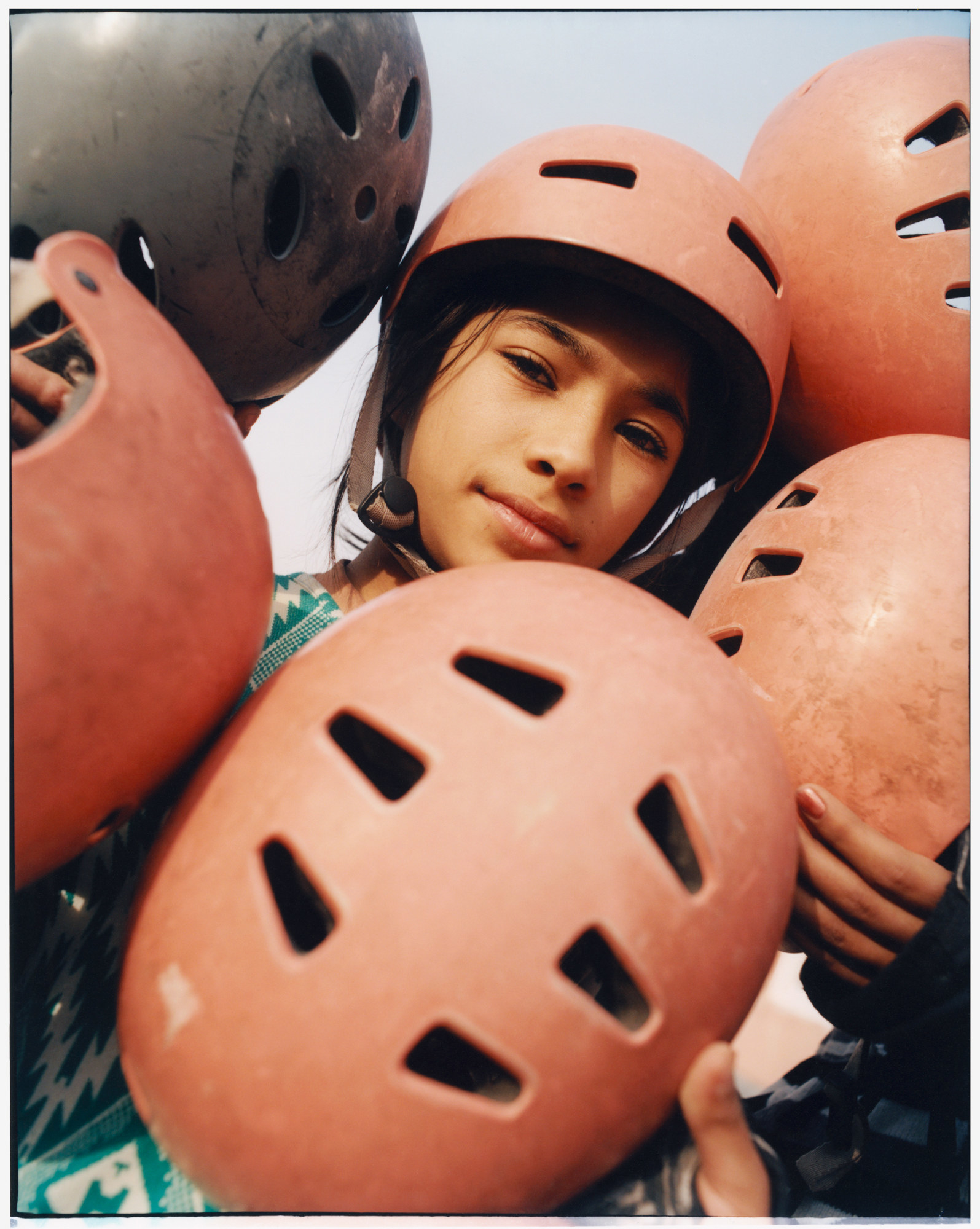 A young girl in a skate helmet surrounded by other helmets