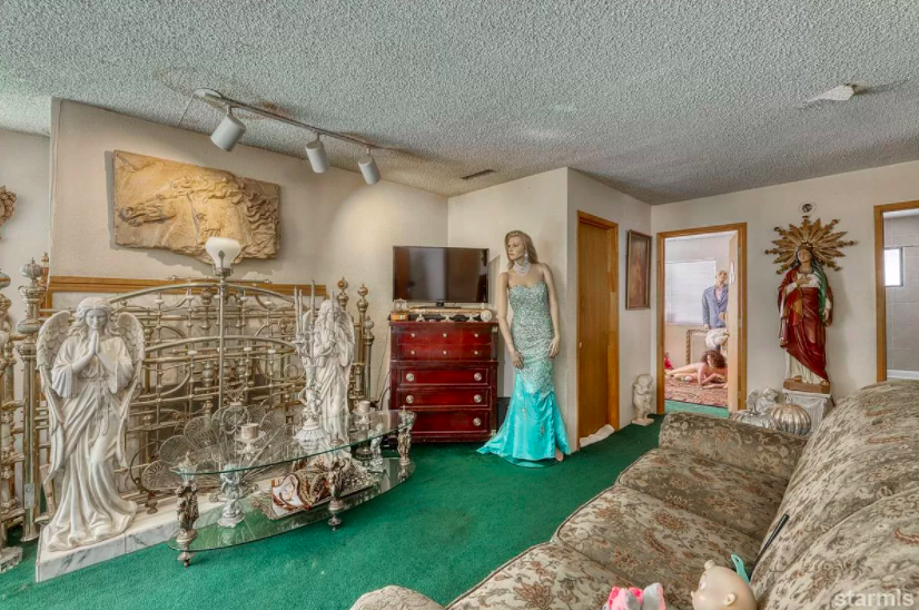 Several tall religious figures are placed around the room as well as some strange dressed up decorative items