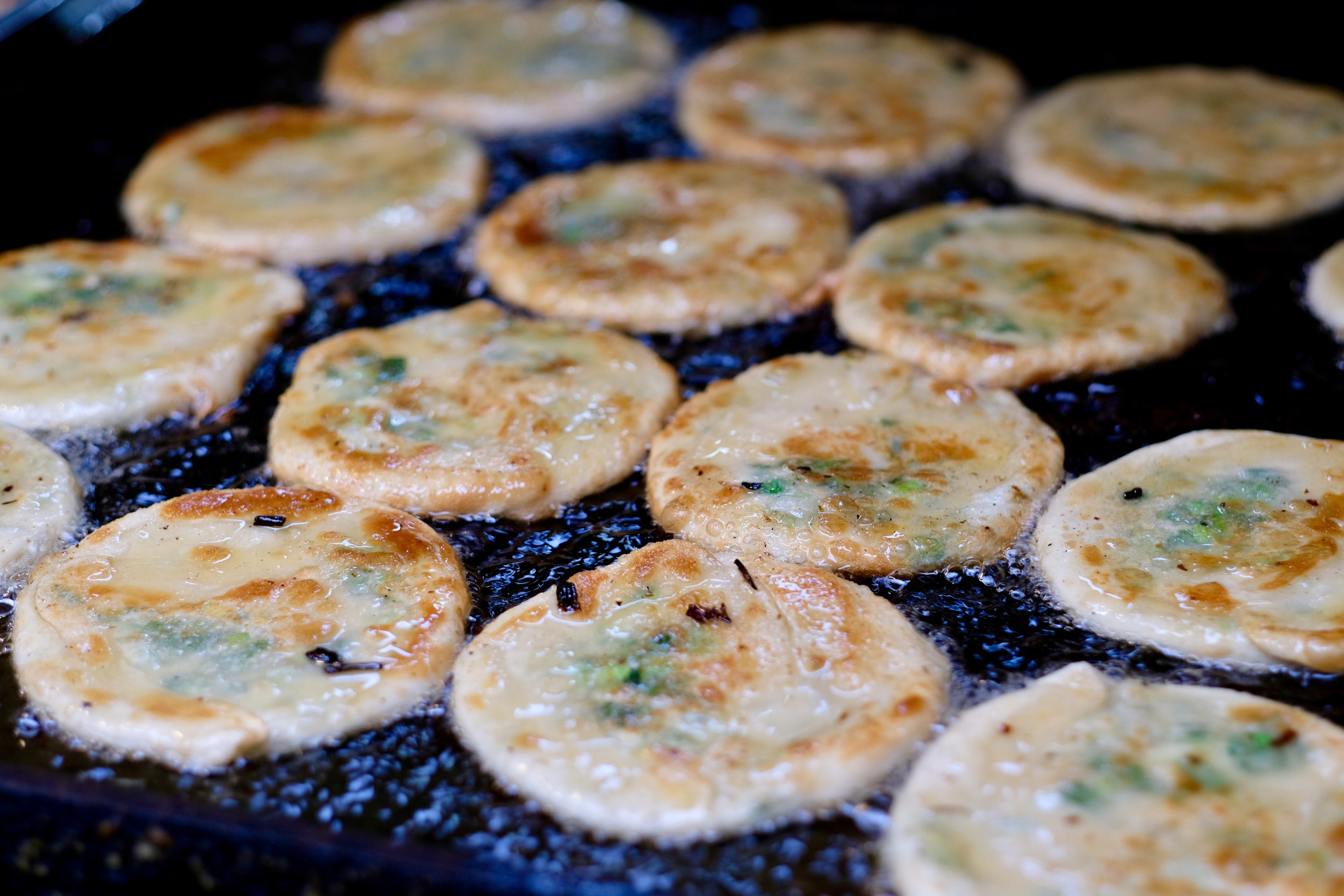 Rows of scallion pancakes fry in oil on a hot pan