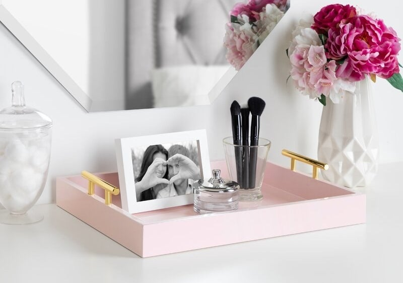 a rectangular pink tray with gold handles on it
