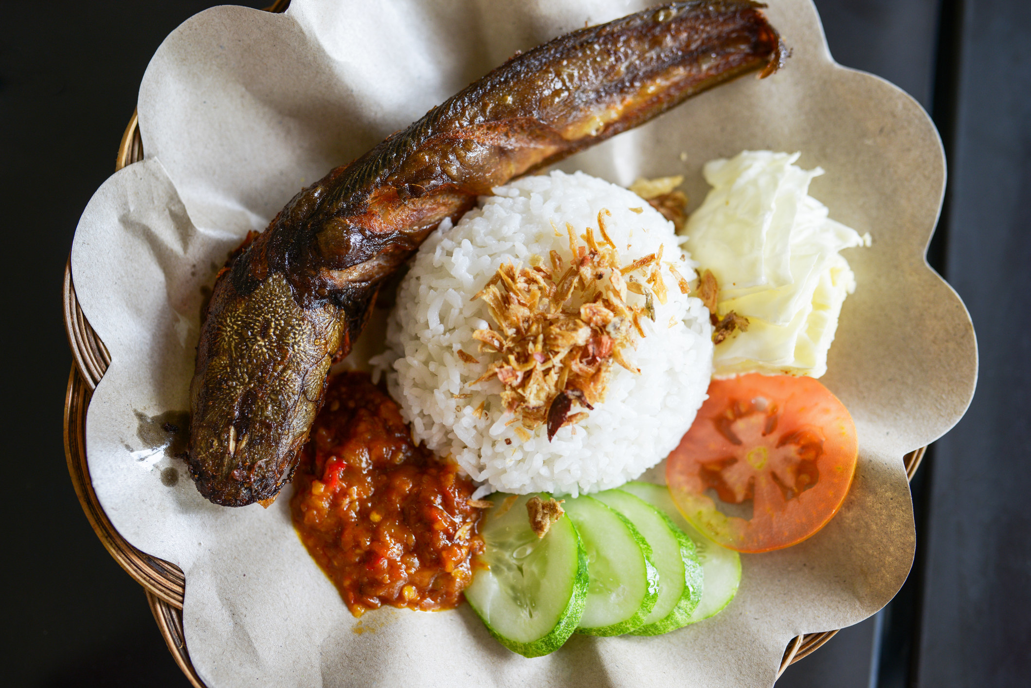 A whole fried fish sits on a plate with a mound of rice, veggies, and a spicy-looking sauce