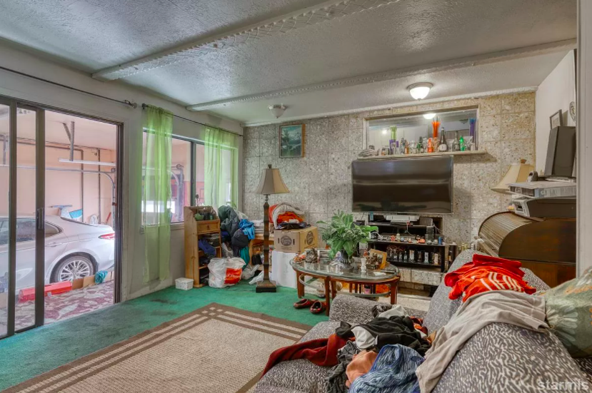 There's a large TV, a couch, table, and other regular household items except the room is right off the garage which you can see into through a sliding door