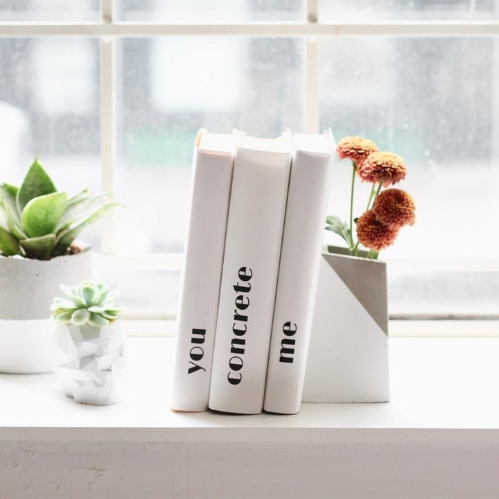 A rectangle-shaped concrete vase that's half white and half gray with books propped against it
