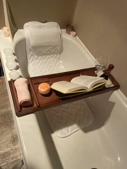 a reviewer photo of the cushion in the tub with a bath tray and bath bomb