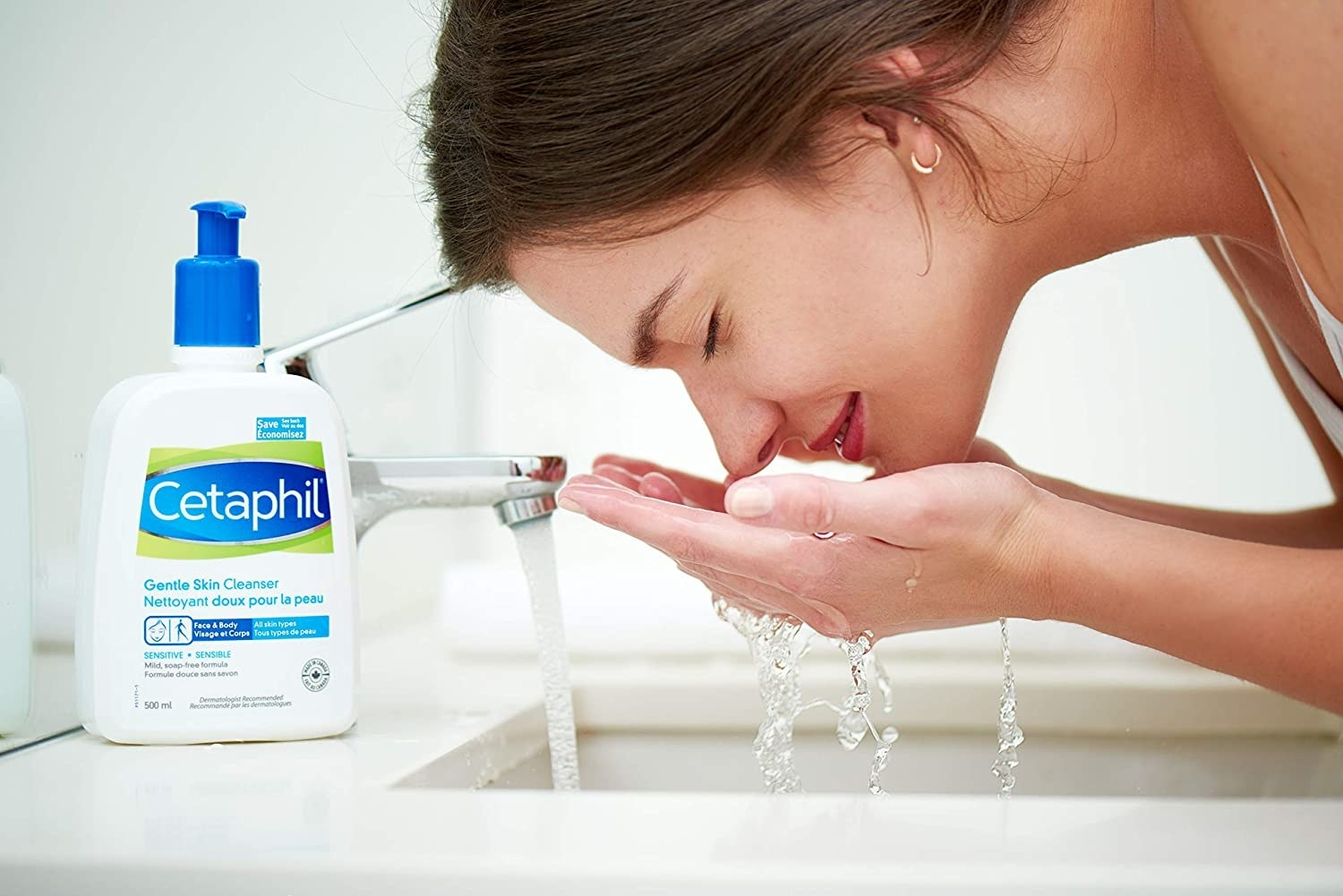 A person washing their face at a bathroom sink with a bottle of cleanser beside them
