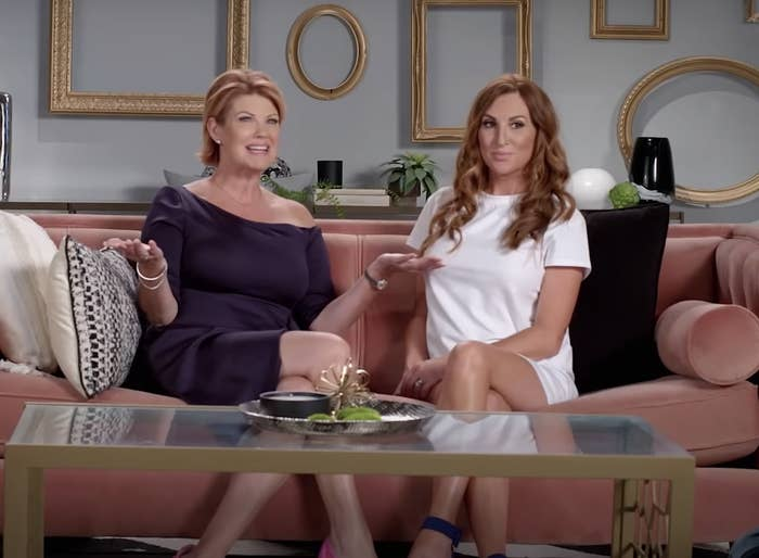 The two hosts sit on a couch together