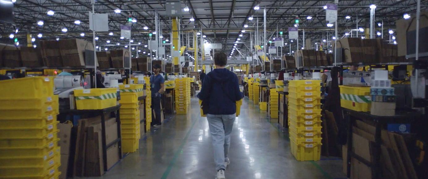 Fern carries a yellow bin down an aisle inside an Amazon packaging facility