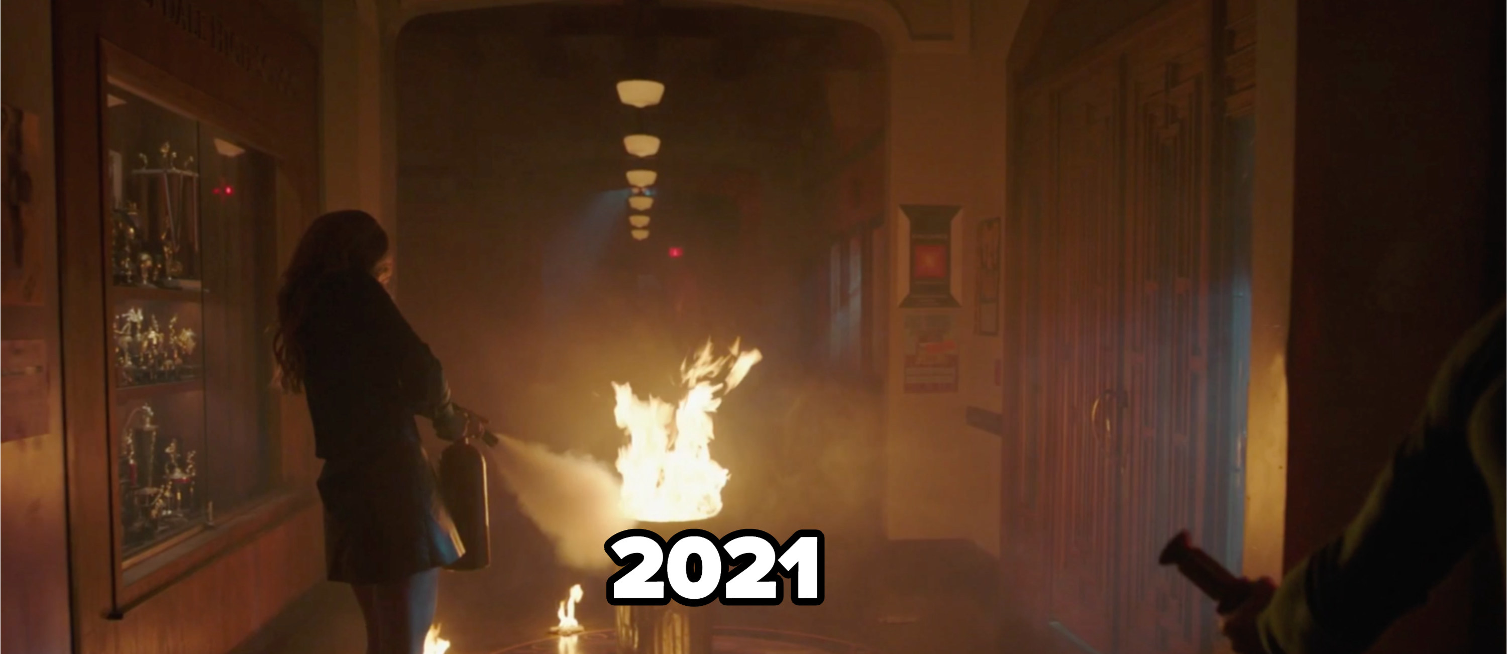 Literally a fire in the school trash captioned '2021' with someone attempting to put it out with a fire extinguisher