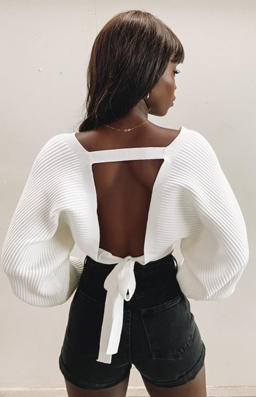 A model seen from the back in the ribbed white sweater