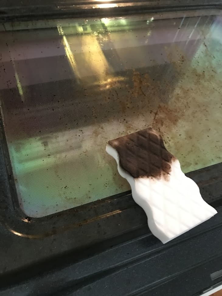 oven glass partially cleaned by very dirty looking magic eraser sponge