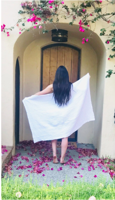 a model walking outside wearing the white bath sheet with flower petals on the ground