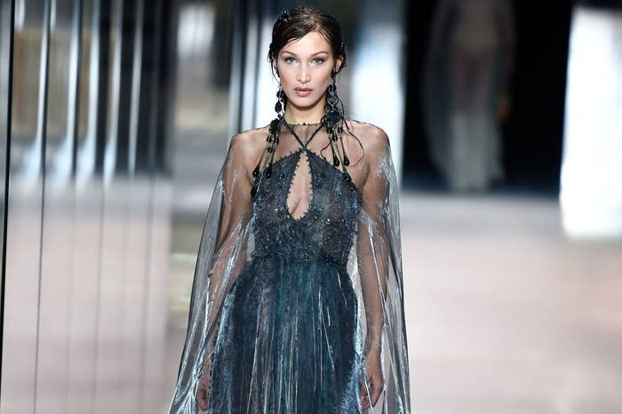 Bella walks a runway in a shimmering blue gown with a keyhole cutout, halter neck and sheer cape