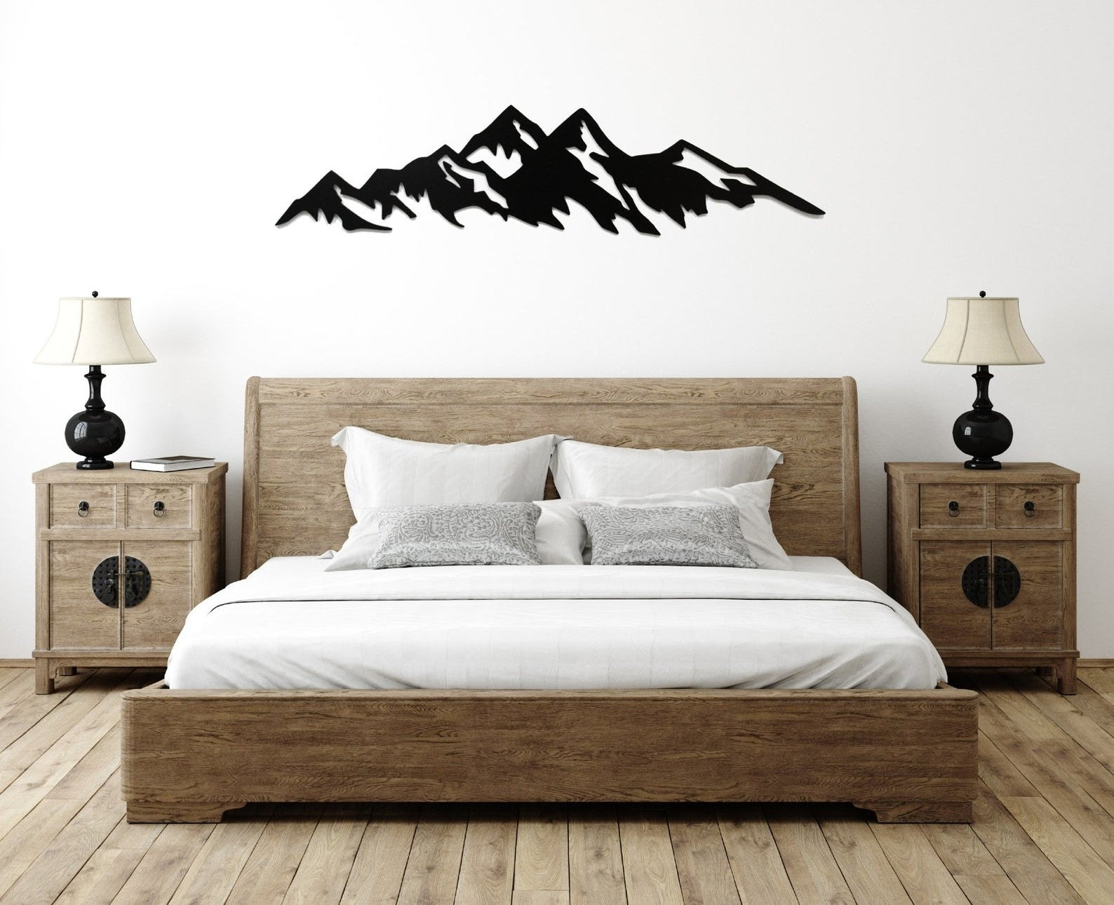A minimalist black metal mountain range installed above a bed