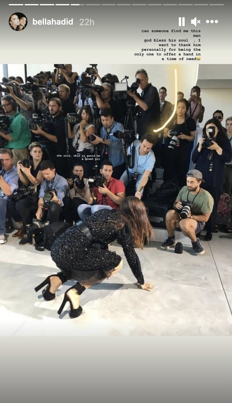 Bella falls to her knees in front of a row of photographers, one who is reaching out his hand
