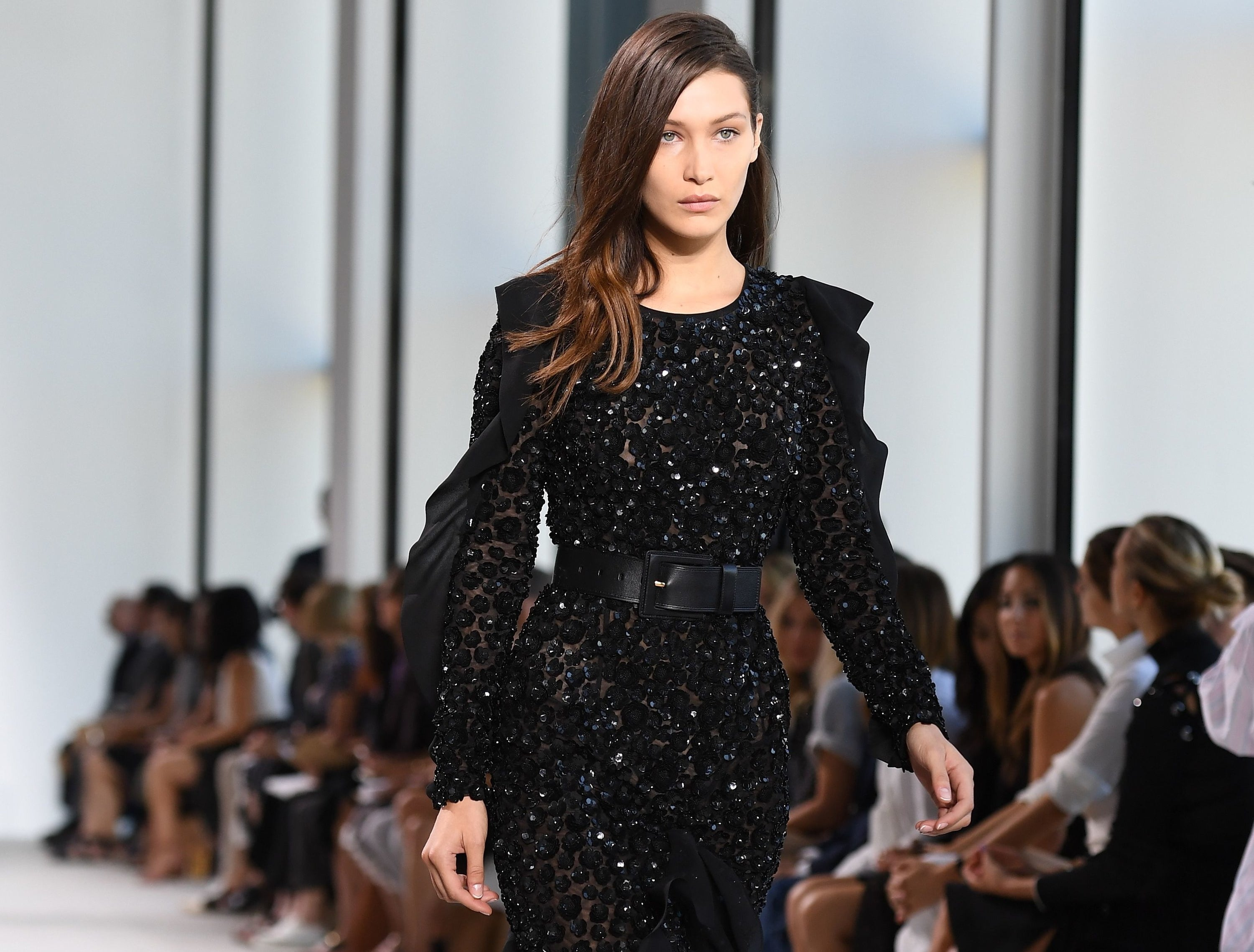 Bella walks in the Kors show in a black sequined long sleeve dress cinched with a black belt