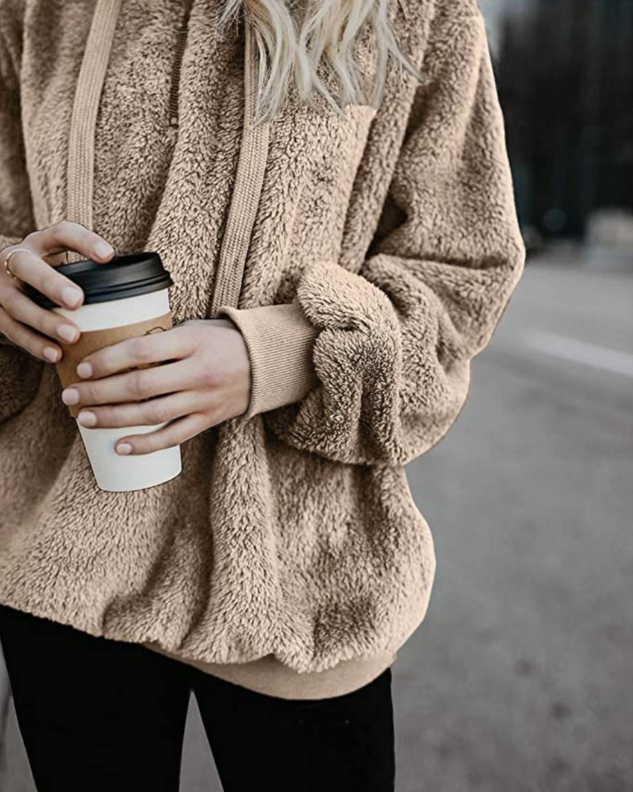 person wearing the hoodie and holding a coffee cup