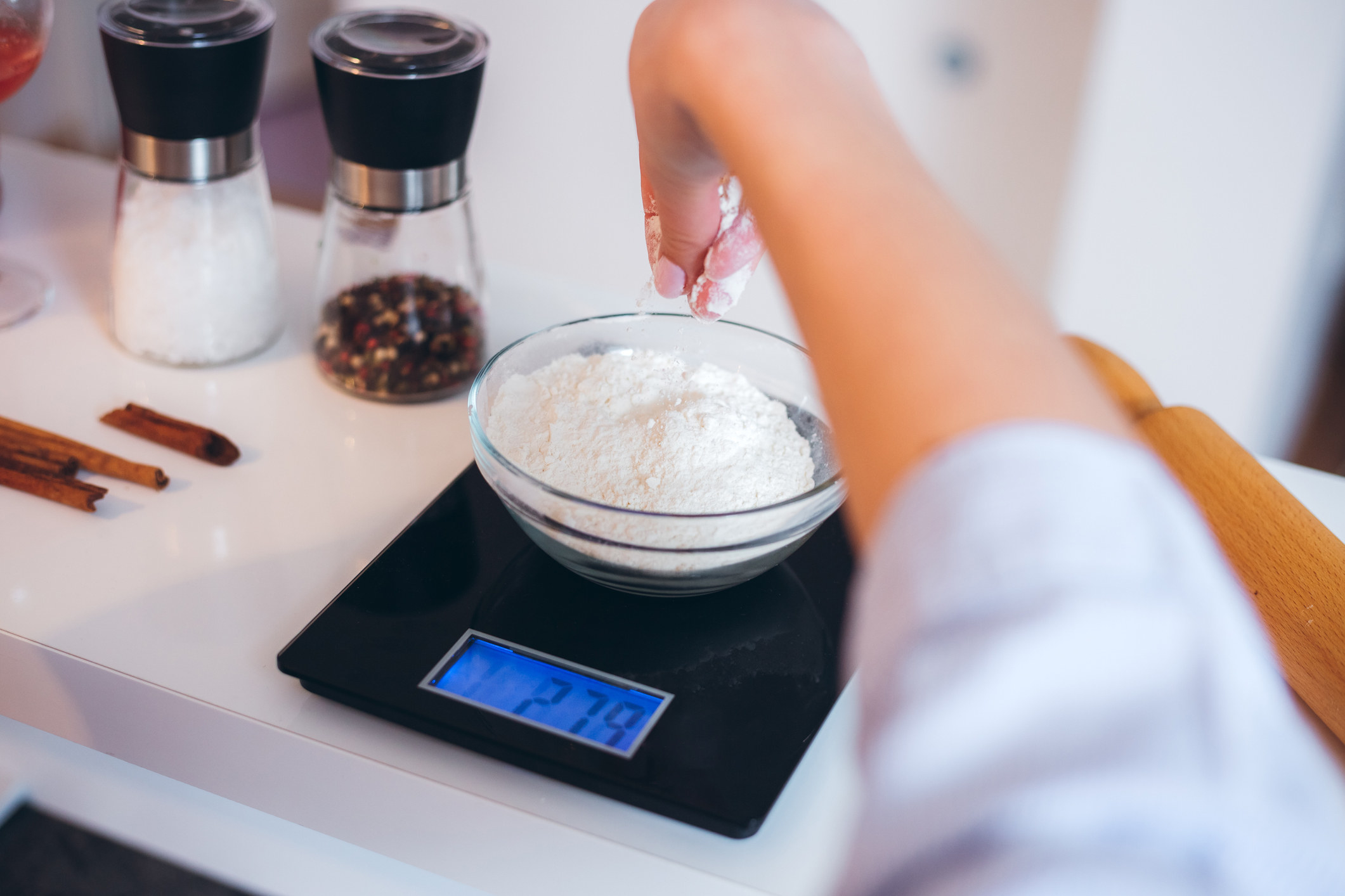 A person weighing some flour on a digital scale
