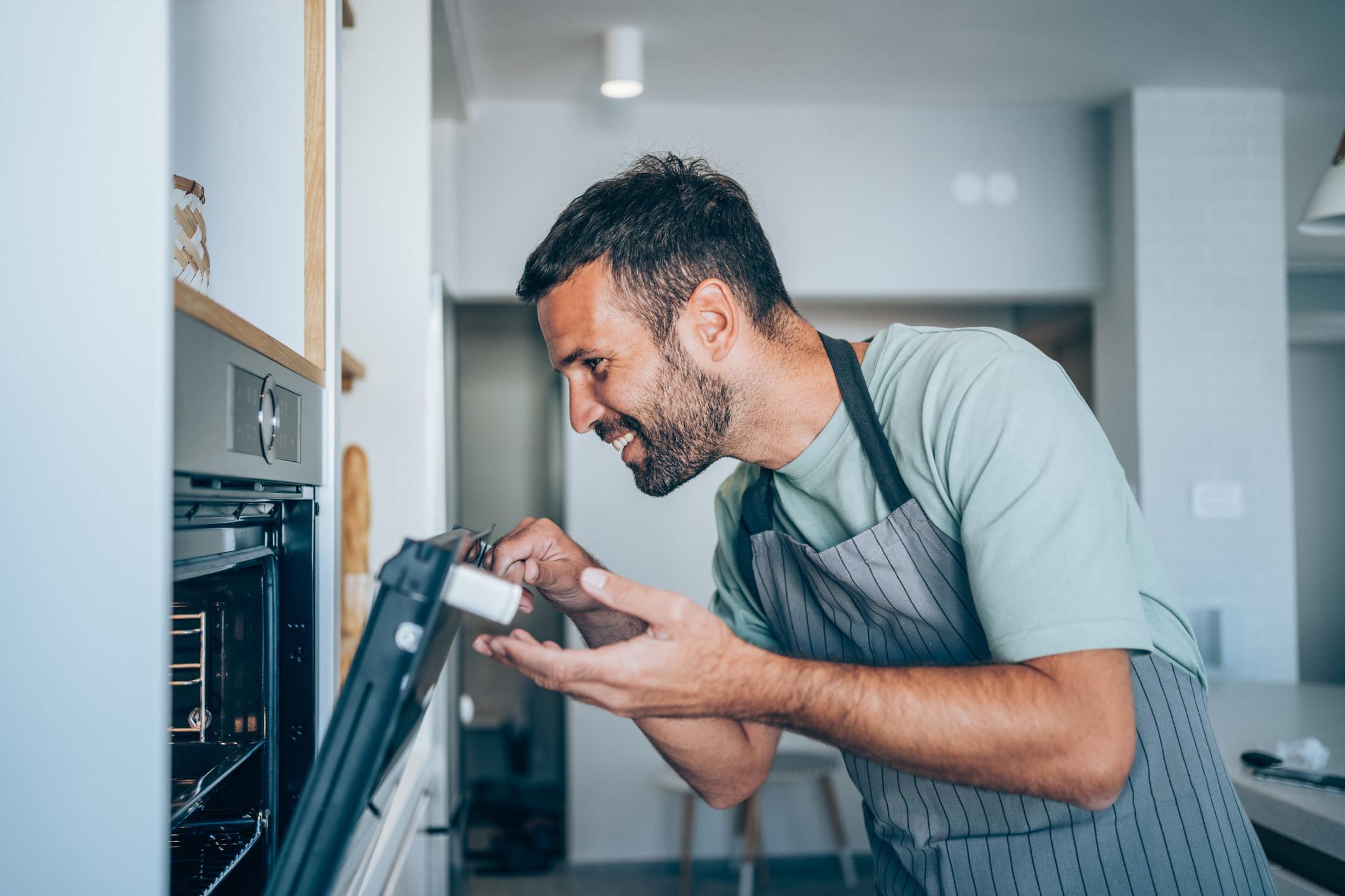 A guy smiling and opening his oven