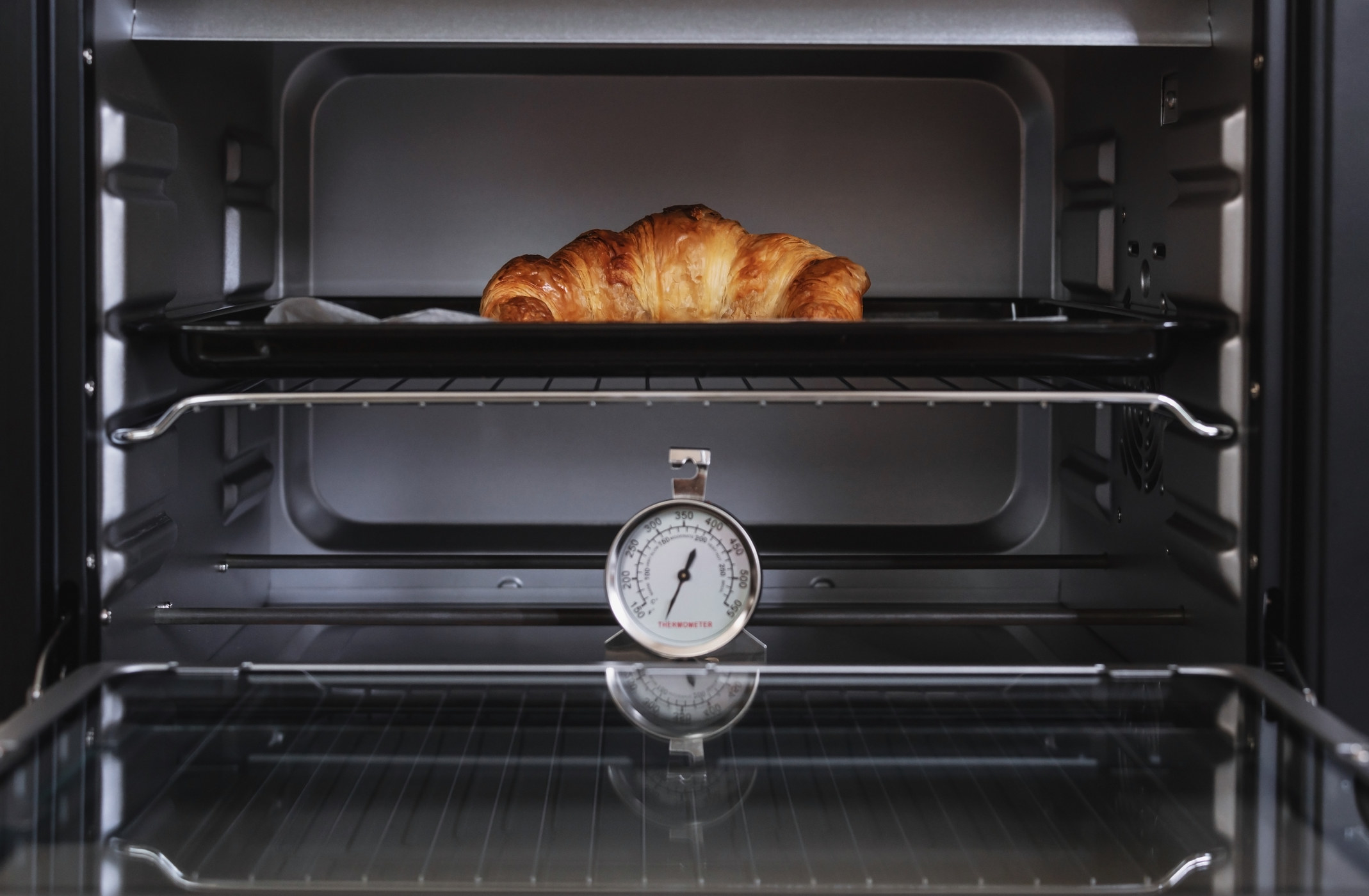 An oven thermometer in the oven as a croissant bakes