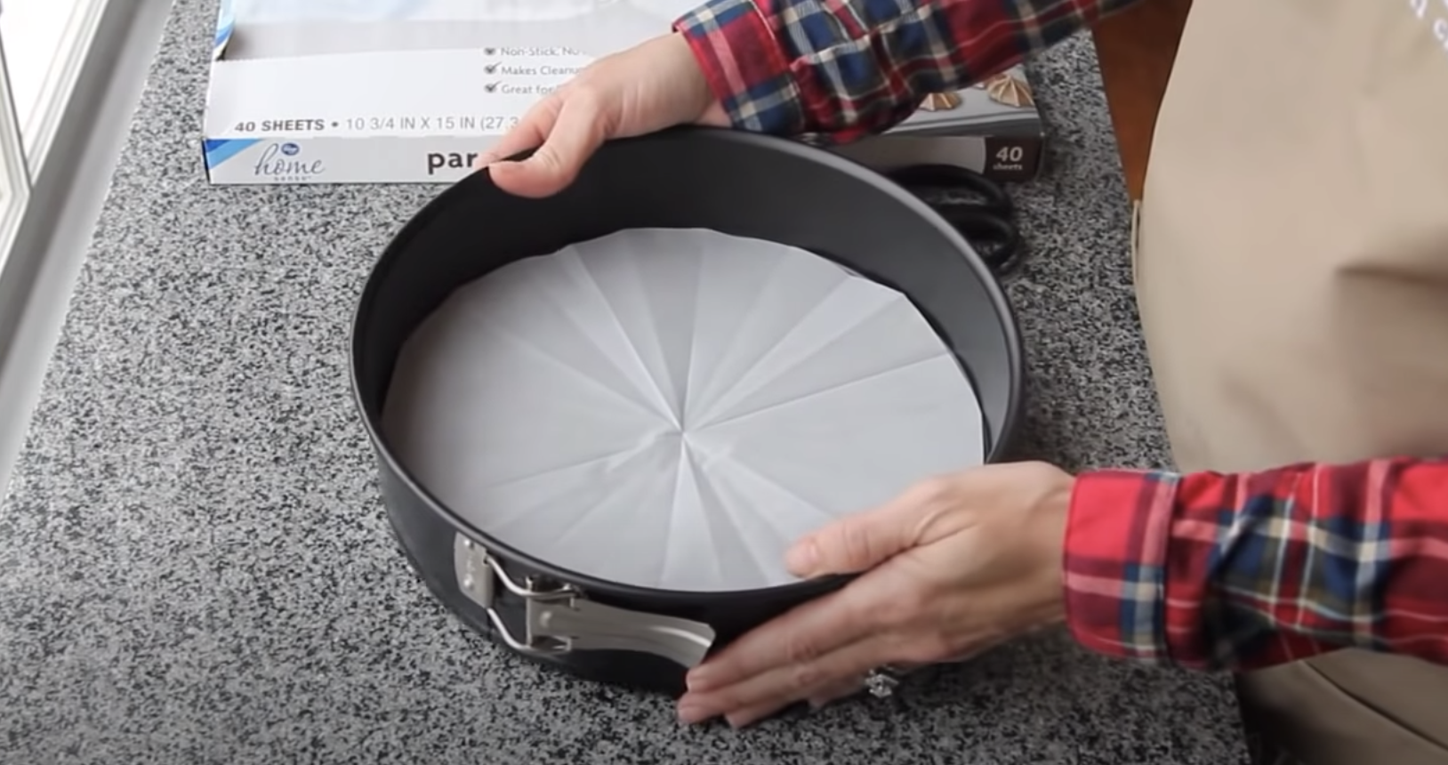 A person lining their cake tin with some parchment paper
