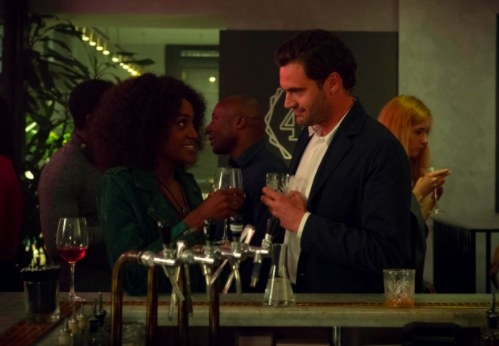 Louise and David stand at a bar facing each other and smiling, they each hold glasses of alcohol