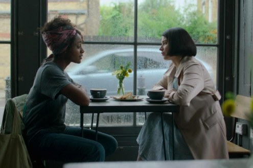 Louise and Adele sit at a small table by a window at a cafe; two cups of coffee and a cake are on the table between them