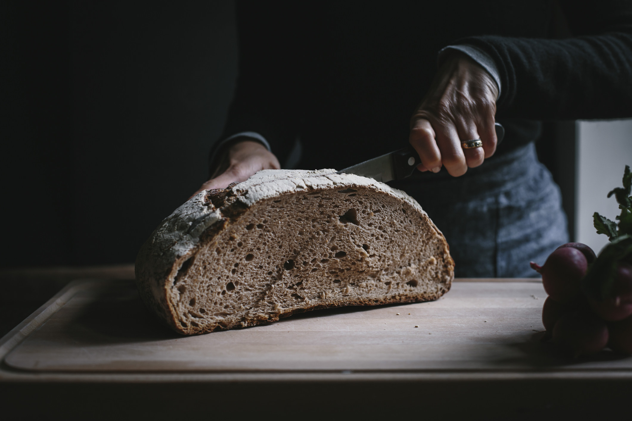 A person slicing into a big bread loaf