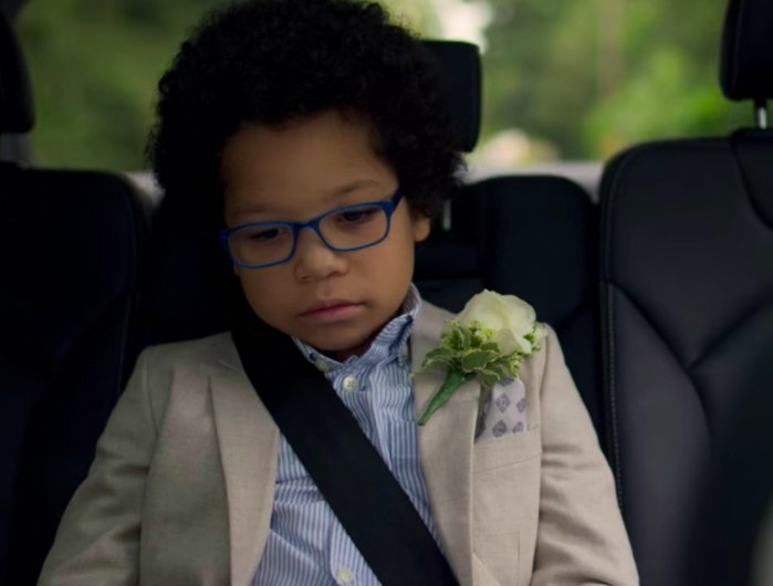 Adam sits in the backseat of a car wearing wedding atire and looking sad