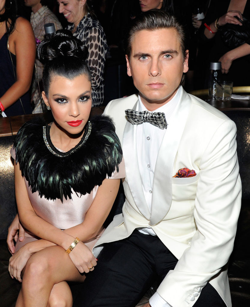 """Kourtney Kardashian, wearing a satin and feathered dress, and Scott Disick, wearing a tux, attend the launch of AG Adriano Goldschmied's """"backstAGe presents:"""""""