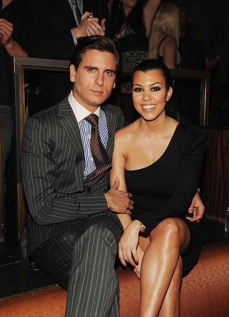 Scott Disick (L) and Kourtney Kardashian sitting at a club in 2010