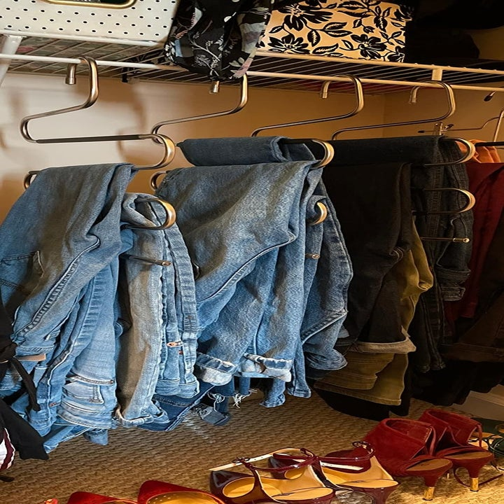 reviewer pic of four of the hangers with lots of jeans on each one