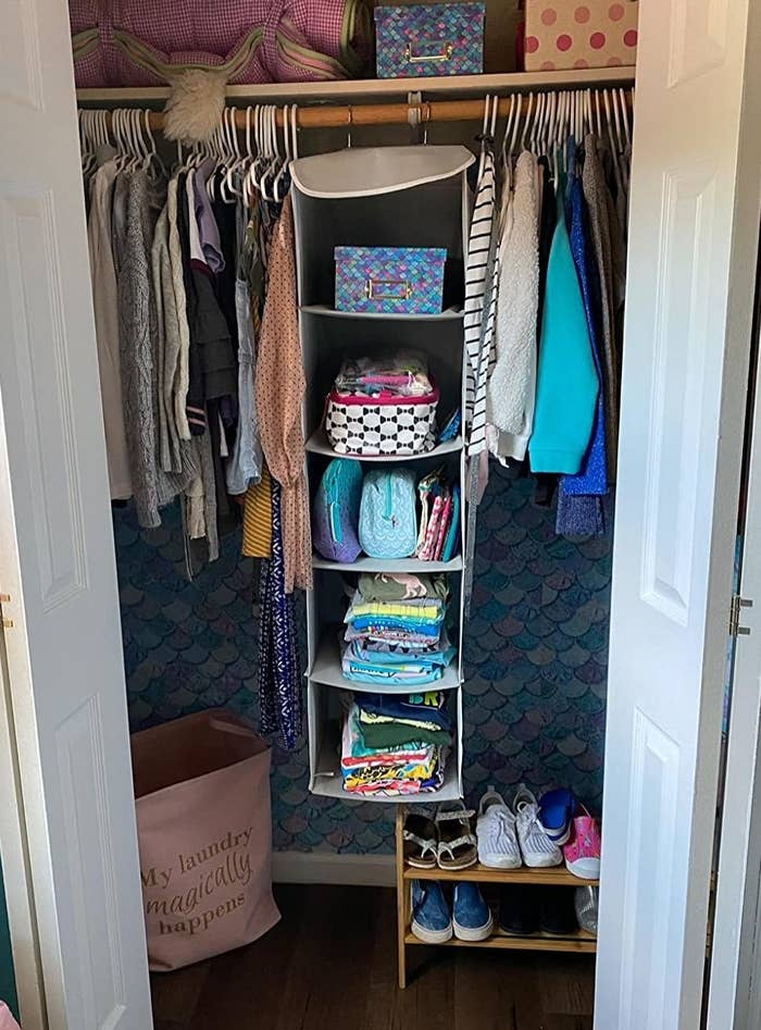 reviewer pic of the five-tier hanging shelf with three mesh pockets on the side hanging in a closet in a bedroom
