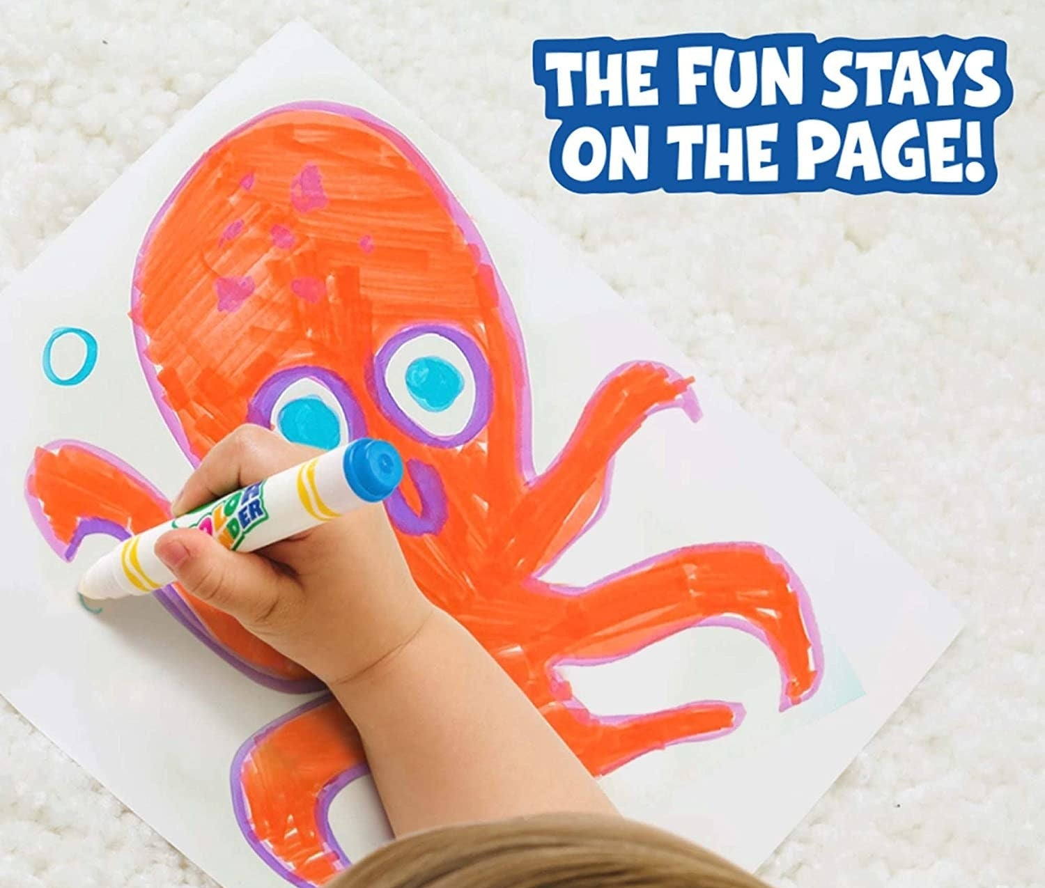 A child's hand colouring a picture of an octopus on a paper