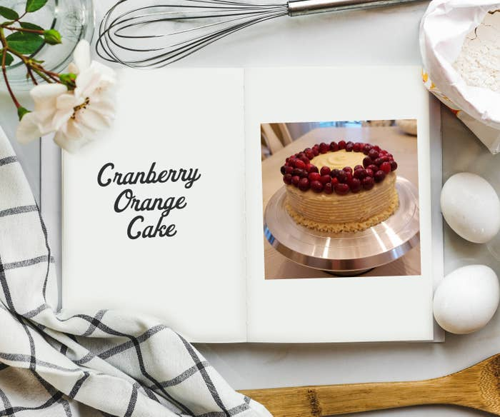 An overhead shot of cookbook on a table surrounded by ingredients and a photo on the inside of a white cake with cranberries surrounding the perimeter.