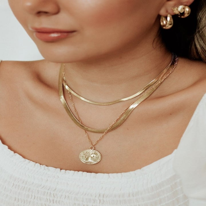 Model wearing snake chain necklace amongst other gold necklaces
