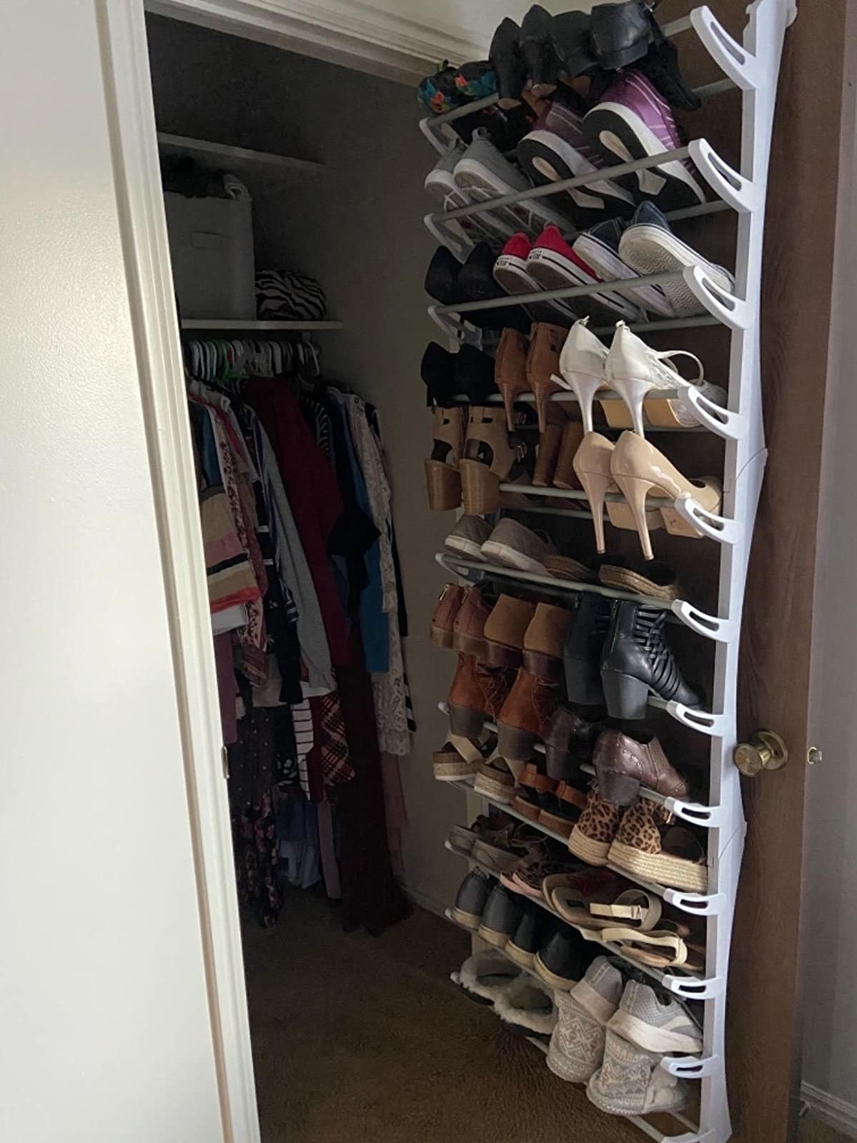 reviewer pic of the shoe rack on the back of a closet door filled with lots of pairs of shoes
