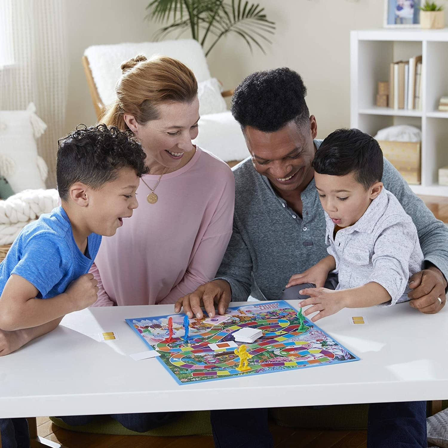 Two adults and two kids sitting in front of a small table with a board game on top