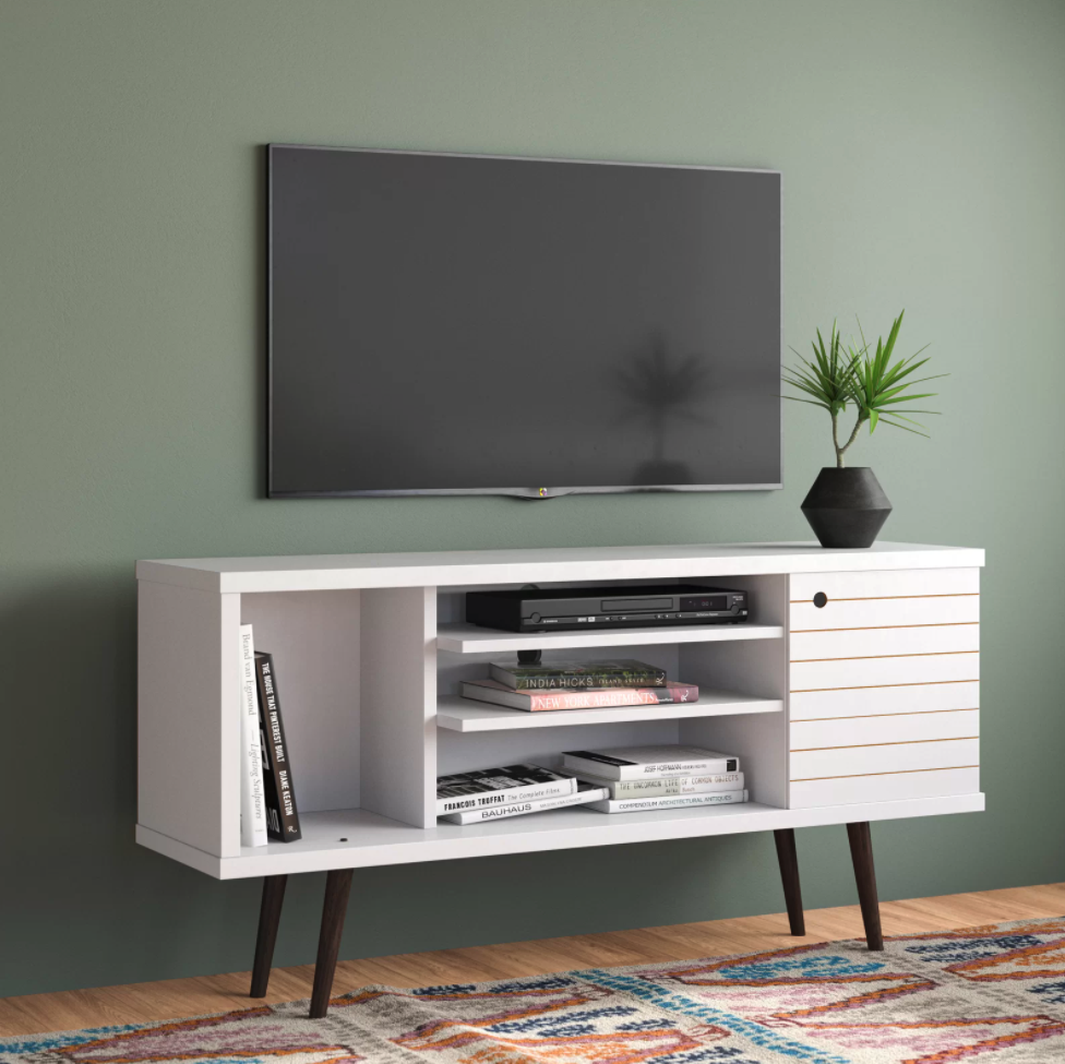 the white tv stand has three shelves, and two cabinets on the ends, one with a door