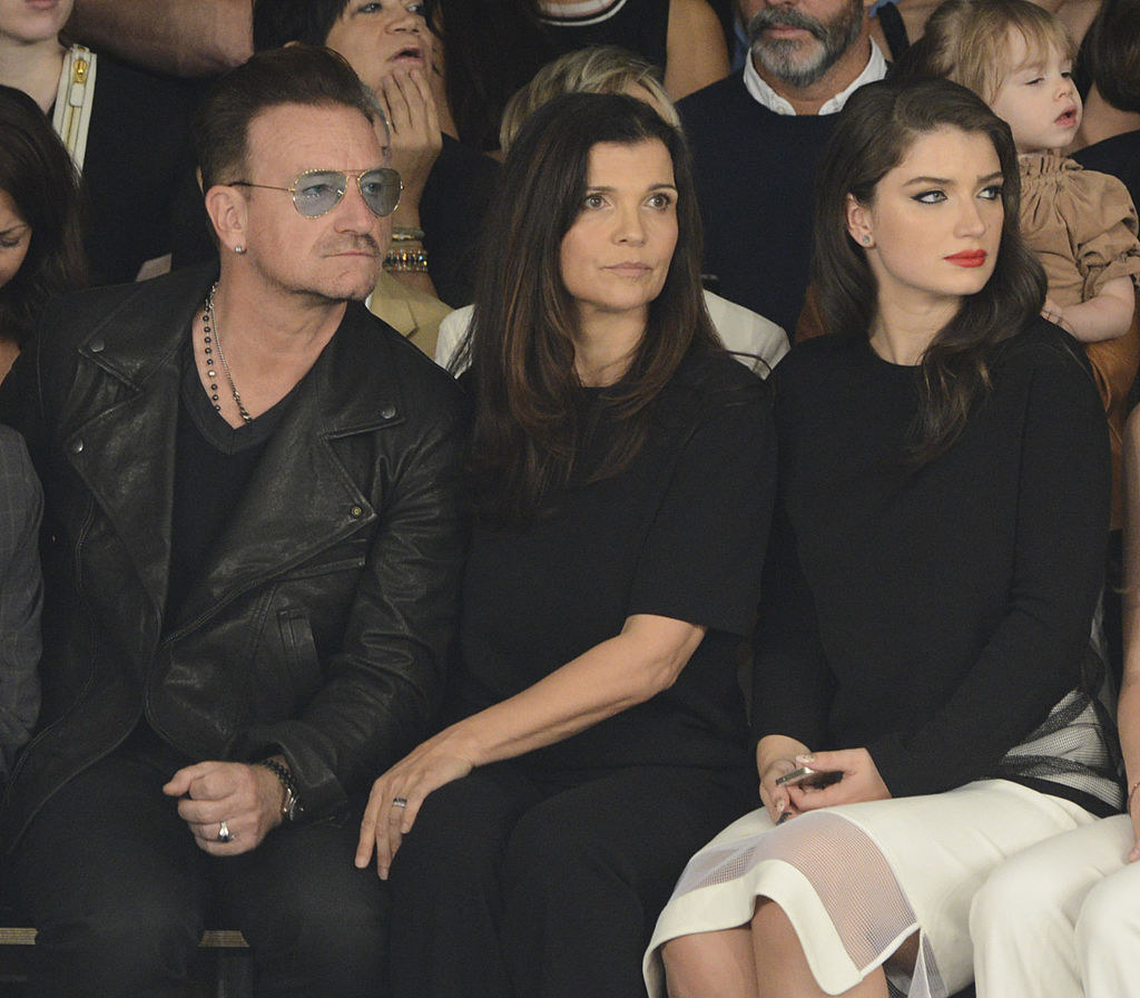 Eve and her parents sitting in the audience of a runway show