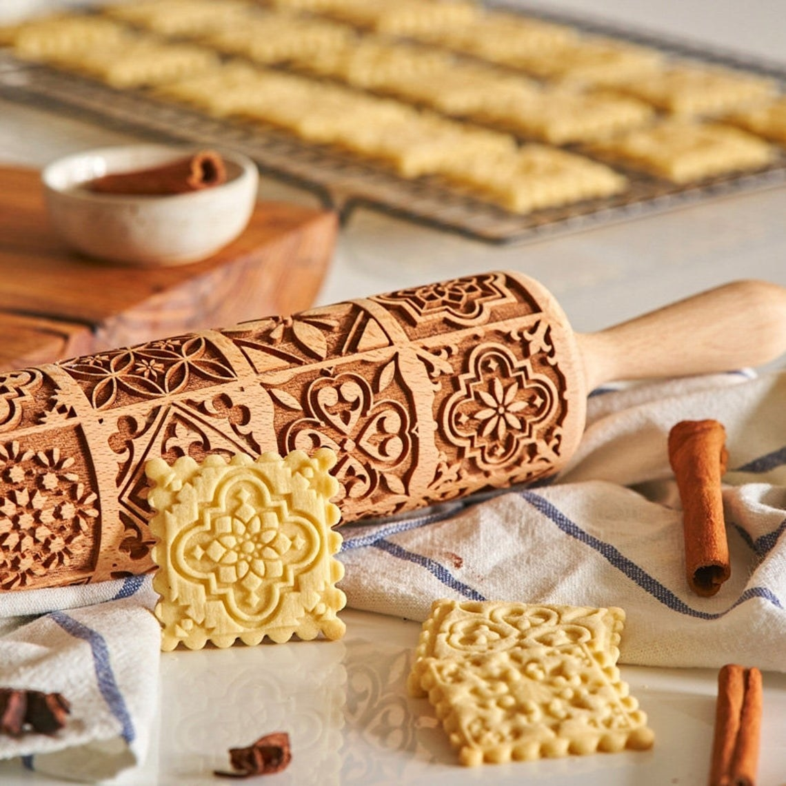 Square butter cookies with intricate vintage patterns made from the rolling pin beside them