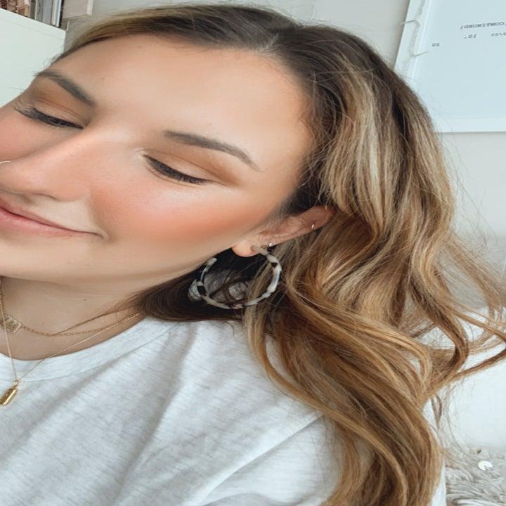 same person wearing tortoise hoop earrings