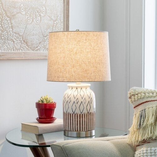 the ceramic lamp with a orange and navy geometric design and a plain beige shade