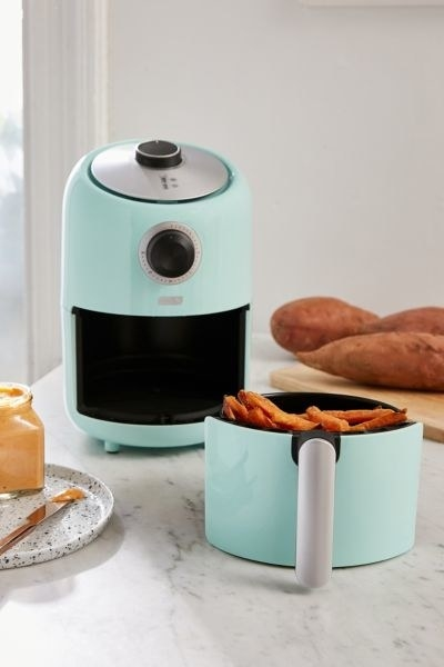 Air fryer with cooked sweet potato fries inside