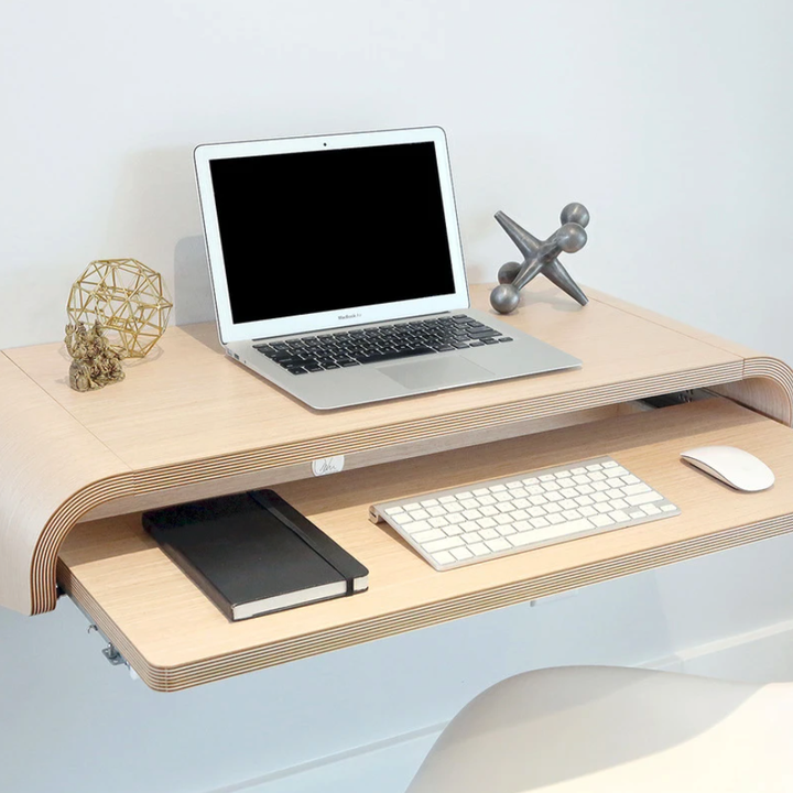 the floating desk with a laptop on it and a pull-out tray with a keyboard, mouse, and notebook on it